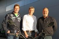 Henning Löw (links, Reaction Deutschland) und Elmar Steck (rechts, Außendienst Koch Zweirad Vertrieb) nehmen Kai Friedrichsen in ihrer Mitte als Vertriebs-Leiter bei Koch Zweirad auf